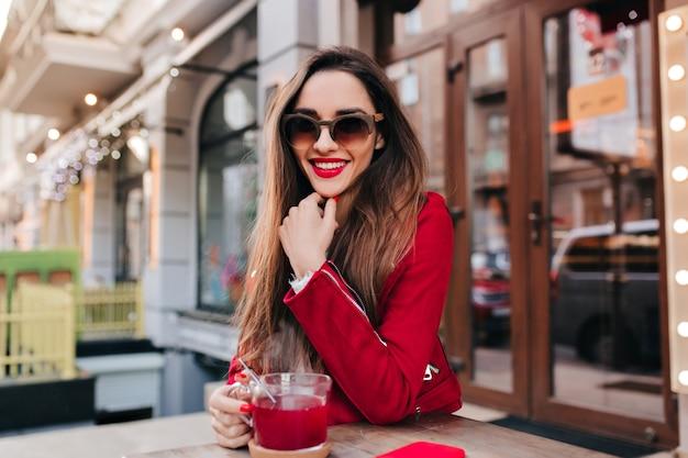 Overweldigend kaukasisch meisje in rood jasje dat in koffie glimlacht