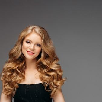Overweldigende blondevrouw met kapsel na het kijken van de kapper