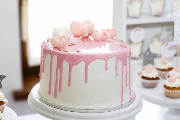 Overweldigende die verjaardagscake met roze suikerglazuur en rozen wordt behandeld