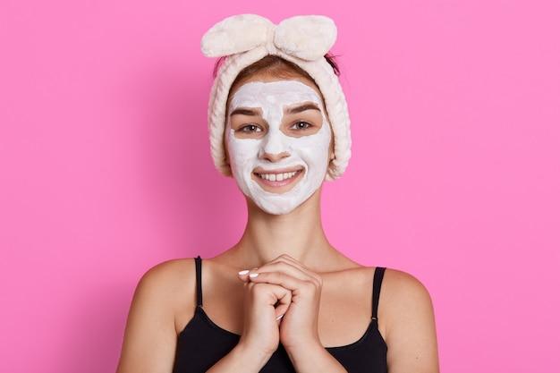 Overweldigende glimlachende donkerbruine vrouw in grappige haarband op hoofd die wit voedend masker of room op gezicht toepast dat over muur wordt geïsoleerd, houdt handen voor borst.