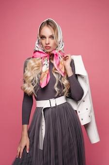 Overweldigende russische schoonheid in hoofddoek. ze houdt een witte leren jas in haar arm achter haar rug. isoleer op roze.