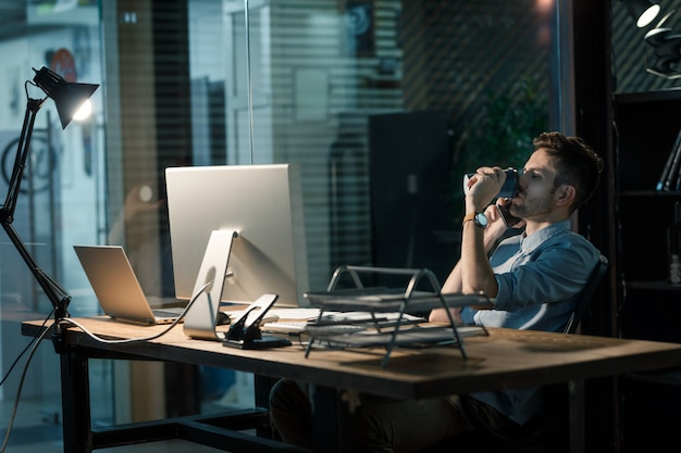 Overwerkende man met koffie spreken op telefoon