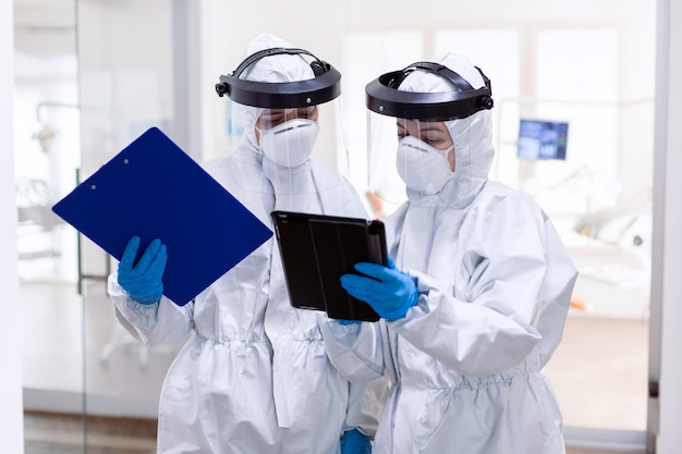 Overwerkt artsenteam dat samenwerkt met het dragen van een pbm-pak in het hospita. medische collega's die professionele uitrusting dragen tegen infectie met coronavirus als veiligheidsmaatregel.