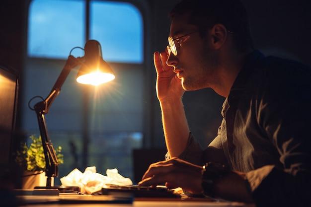 Overwerkt. man die alleen op kantoor werkt tijdens quarantaine van coronavirus of covid-19 en tot laat in de nacht blijft. jonge zakenman, manager die taken doet met smartphone, laptop, tablet in lege werkruimte.