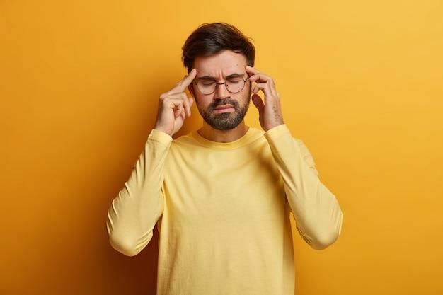 Overwerkte gefrustreerde bebaarde man masseert tempels, lijdt aan ernstige migraine, sluit ogen om pijn te verlichten, draagt optische bril en casual gele trui, staat erin, probeert te kalmeren