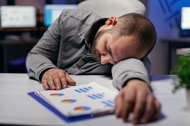 Overwerkte hardwerkende zakenman die hoofd op de tablet rust. workaholic-medewerker die in slaap valt omdat hij 's avonds laat alleen op kantoor werkt voor een belangrijk bedrijfsproject.