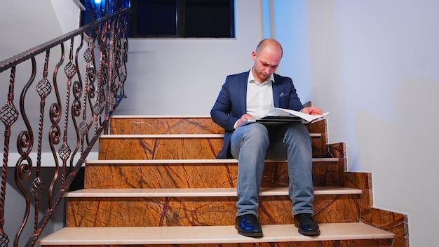 Overwerkte kantoormedewerker die 's avonds laat op de trap in een modern bedrijfsgebouw de jaarlijkse grafieken controleert. bedrijfsmanager die overtijd aan het werk is om het project van de zakelijke deadline af te werken en documenten te analyseren.