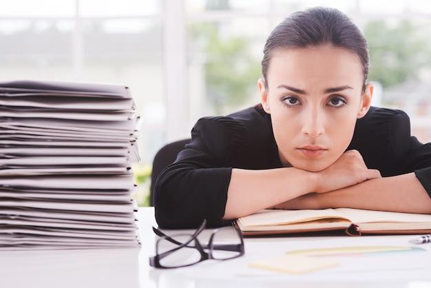 Overwerkte leidinggevende. depressieve jonge vrouw in formalwear kijkt naar de camera en leunt met haar gezicht aan de tafel met een stapel documenten die dichtbij liggen