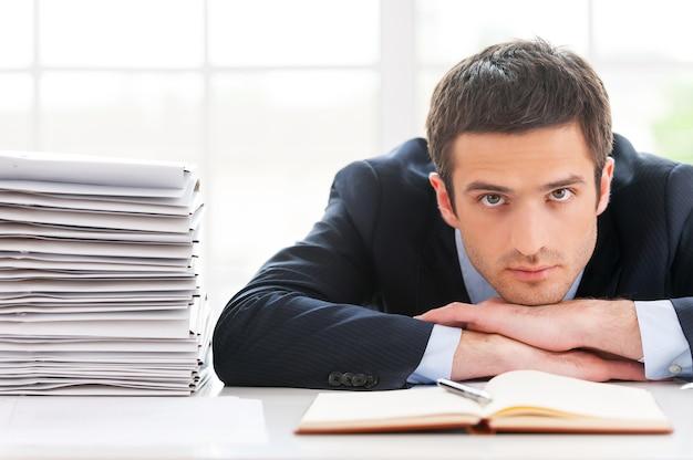 Overwerkte leidinggevende. depressieve jongeman in formele kleding die naar de camera kijkt en met zijn gezicht aan de tafel leunt met een stapel documenten naast hem