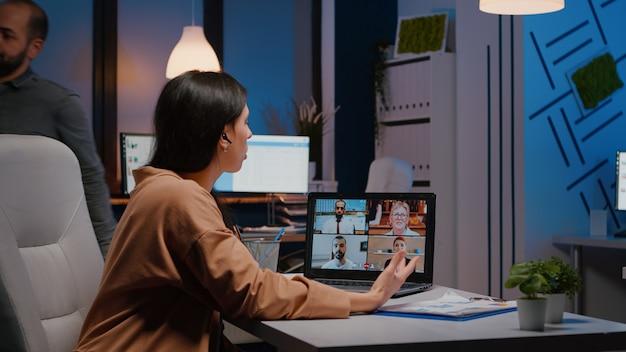 Overwerkte manager die in een opstartend bedrijfskantoor werkt en bespreekt met virtueel teamwerk