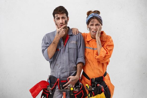 Overwerkte ongelukkige bebaarde reparateur en zijn vrouwelijke assistent,