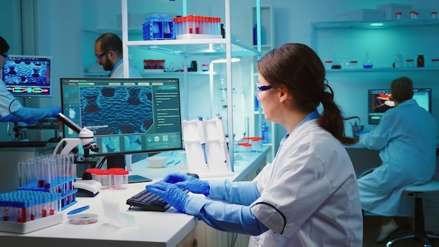 Overwerkte scheikundige zit in een modern uitgerust laboratorium en kijkt moe naar de camera
