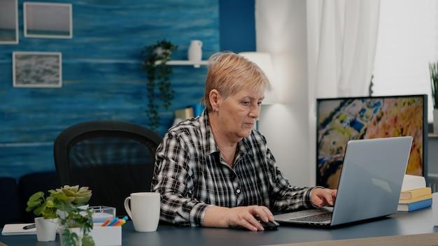 Overwerkte senior vrouw die thuis werkt op laptop lezen schrijven zoeken analyseren statistieken f...