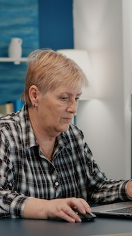 Overwerkte senior vrouw die thuis werkt op laptop