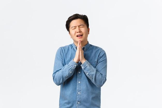 Overwerkte sombere en trieste aziatische man die om hulp smeekt, handen bij elkaar houdt over de borst in een biddend gebaar, om gunst vraagt, berouw toont, staande witte achtergrond overweldigd.