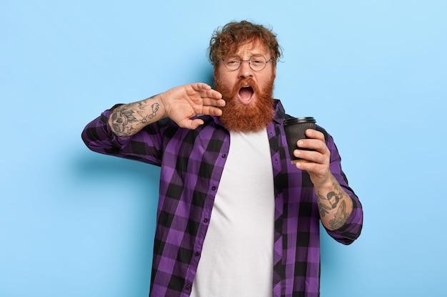 Overwerkte stijlvolle gember man poseren tegen de blauwe muur