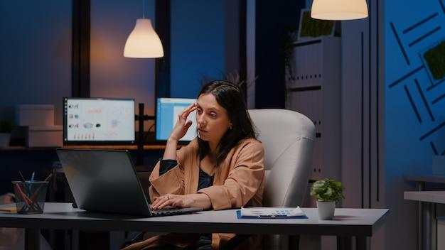 Overwerkte uitgeputte zakenvrouw die 's avonds laat in een opstartkantoor werkt en de managementstrategie op de laptop controleert