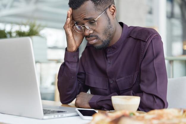 Overwerkte vermoeide donkere man met gefrustreerde uitdrukking, kijkt wanhopig naar het scherm van de laptop, werkt aan een zakelijk project, drinkt koffie om zich niet slaperig te voelen.