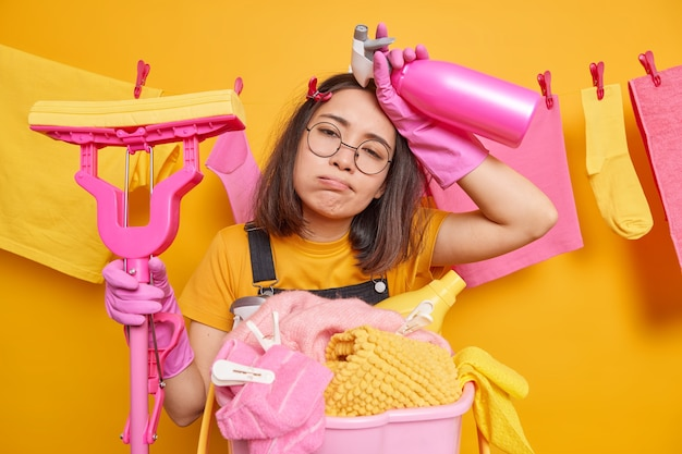 Overwerkte vermoeide jonge aziatische huisvrouw zucht van vermoeidheid houdt dweil en schoonmaakmiddel vast bezig om aan huis te werken doet wassen of wasgoed draagt een ronde bril en vrijetijdskleding