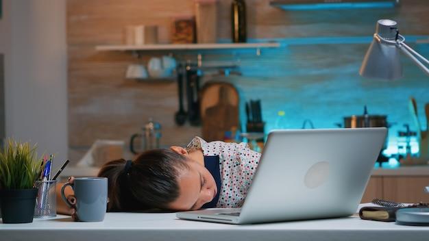 Overwerkte vermoeide vrouw die vanuit huis werkt en in slaap valt op het bureau voor de laptop. drukke gefocuste werknemer die gebruik maakt van moderne technologienetwerken die overuren maken, ogen sluiten en op tafel slapen.