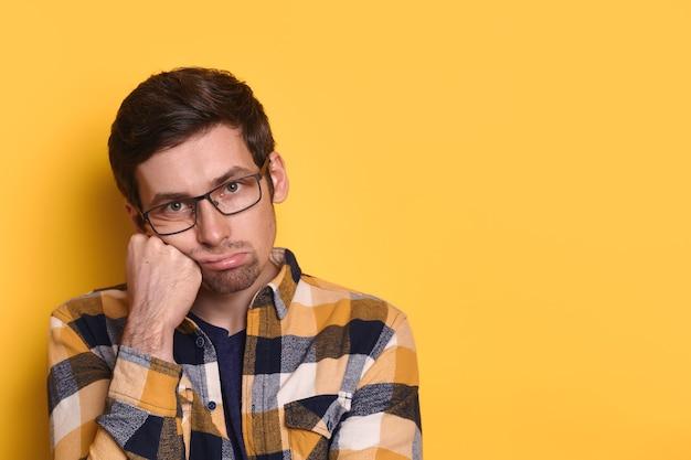 Overwerkte verveelde ongelukkige man kijkt naar camera, houdt hand op wang, geïsoleerd dan geel