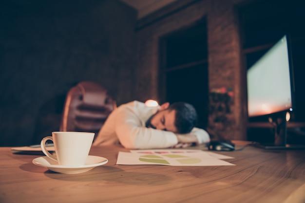 Overwerkte workaholic man slaapt op het bureau voelt zich moe