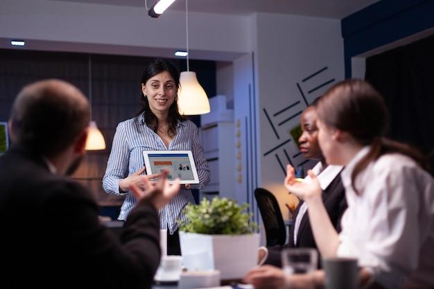 Overwerkte workaholic ondernemersvrouw die marketinggrafieken toont met behulp van tablet