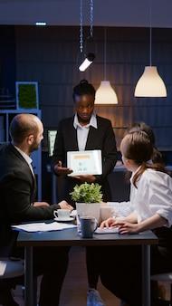 Overwerkte workaholic zakenvrouw met donkere huid die managementgrafieken uitlegt
