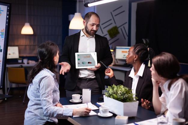 Overwerkte zakenman die financiële grafieken toont met behulp van bedrijfsideeën voor brainstormen op tablets