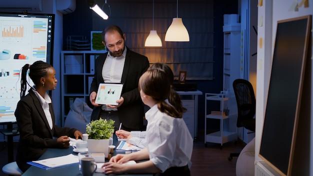 Overwerkte zakenman die financiële grafiekenpresentatie toont die tablet gebruiken