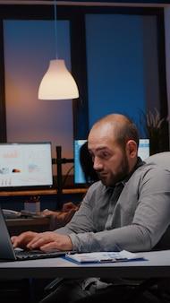 Overwerkte zakenman die managementstrategie typt op laptop die in een startend bedrijf werkt