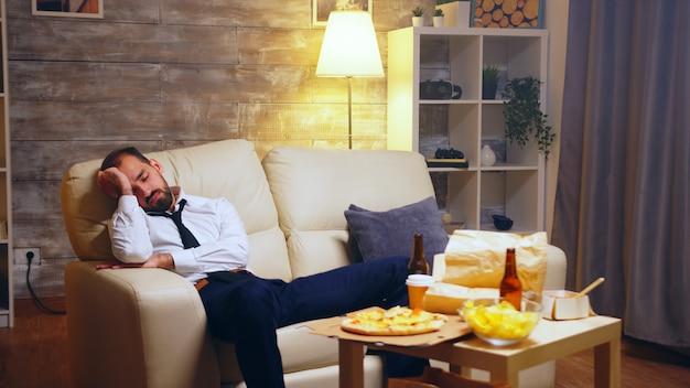 Overwerkte zakenman slapen op de bank met tv aan en junkfood op tafel.