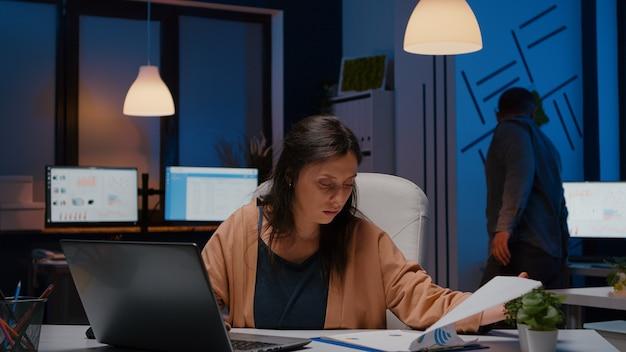 Overwerkte zakenvrouw die financiële grafieken op klembord analyseert