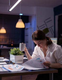 Overwerkte zakenvrouw die 's avonds overwerkt in de vergaderruimte van het bedrijfsbureau