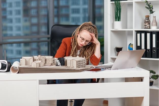 Overwerkte zakenvrouw die stress voelt over enkele problemen met architecturaal en ontwerpproject van toekomstig gebouw.