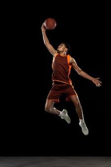 Overwin jonge doelgerichte africanamrican basketbalspeler die aan het oefenen is