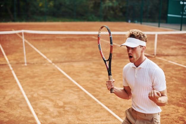 Overwinning vieren. jonge tennisser in sportieve kleding is buiten op het veld.