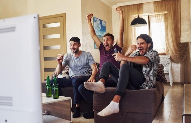 Overwinning vieren. opgewonden drie vrienden die samen thuis voetbal kijken op tv.