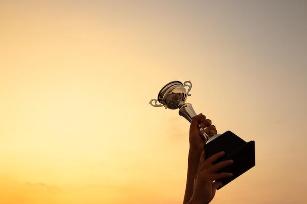 Overwinningsconcept met een hand die een trofee op de achtergrond van de zonsonderganghemel houdt