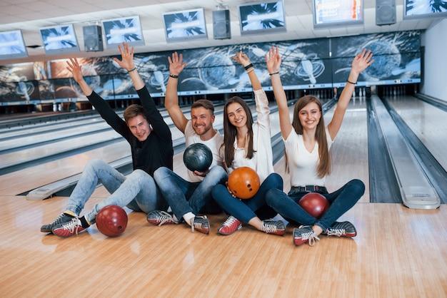 Overwinningspositie. jonge, vrolijke vrienden vermaken zich in het weekend in de bowlingclub