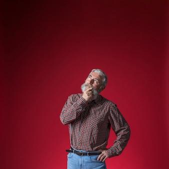 Overwogen hogere mens die met hand op zijn kin omhoog tegen rode achtergrond kijkt