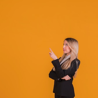 Overwogen jonge onderneemster die haar vinger tegen een oranje achtergrond richt