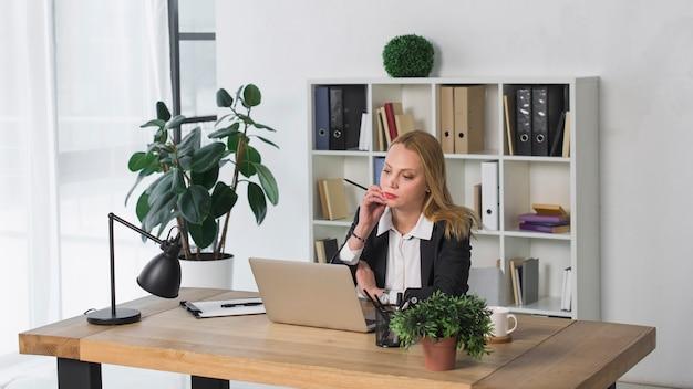 Overwogen jonge onderneemster die laptop in het bureau bekijkt