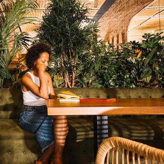 Overwogen jonge vrouw zit aan restaurant tafel met digitale tablet; mobiel en dagboek