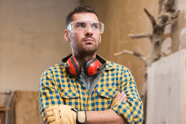 Overwogen mannelijke timmerman veiligheidsbril dragen die zich met haar gekruiste wapens bevinden