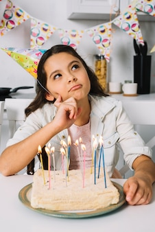Overwogen meisje met haar verjaardagstaart thuis