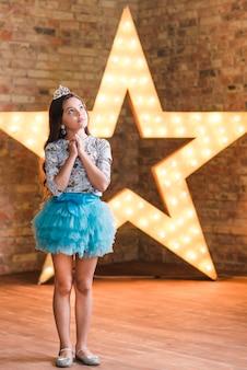 Overwogen schattig meisje staande voor grote ster tegen bakstenen muur