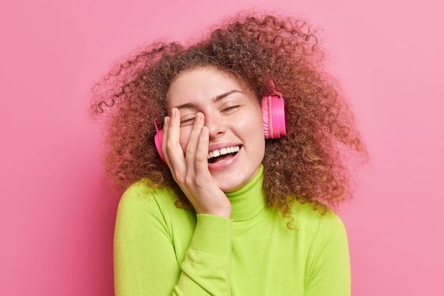 Overyoyed tienermeisje met krullend hbushy haar glimlacht breed houdt hand op gezicht sluit ogen van plezier geniet van het luisteren naar muziek via draadloze koptelefoon gekleed terloops geïsoleerd op roze muur