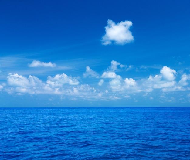 Overzees en blauwe hemel. blauw zeewater en lucht met witte pluizige wolken. horizontale achtergrond van blauwe zee. tropisch landschap