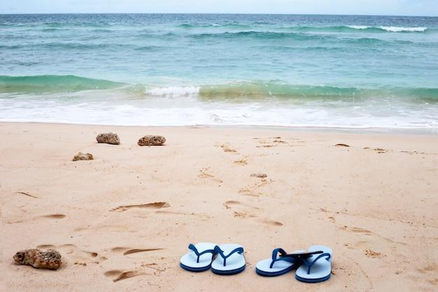 Overzees en golf met blauwe hemel. flip flops op strand